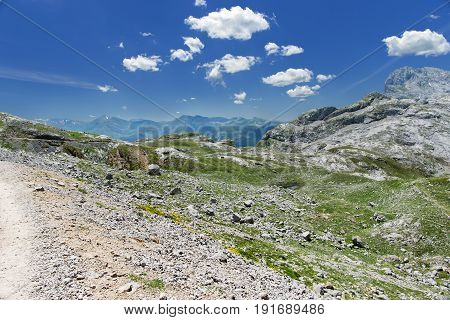 Look in mountains in national park of Picos de Europa Fuente De. Sunny summer day mountains blue sky stony track