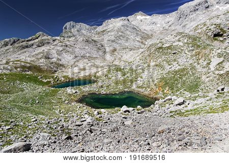 Look in mountains in national park of Picos de Europa Fuente De. Sunny summer day mountains blue sky stony track and two lakes