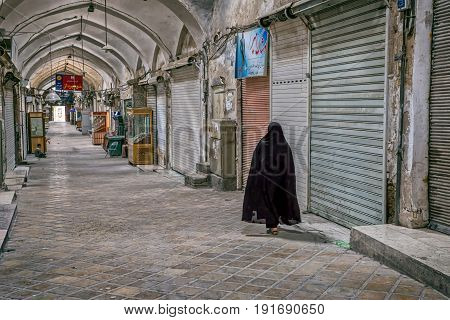 YAZD, IRAN - MAY 5, 2015: A woman wearing traditional clothes passes bazaars empty street in the old part of the city during afternoon break.