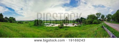 Stitched panorama of summer field with river