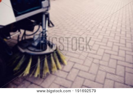 Blurred background unfocus street sweeper machine cleaning the streets. Concept clean streets from debris.