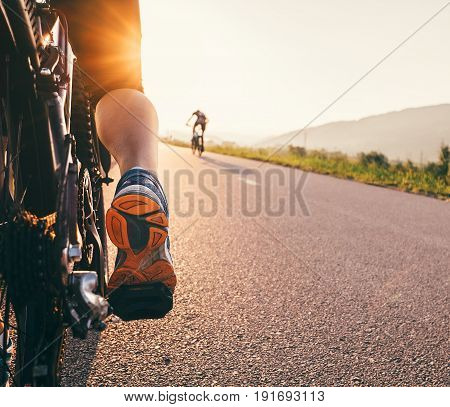 Feet on bycikle pedal in sunset light - close up image