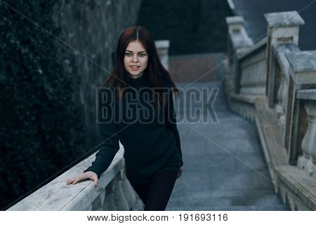 The woman clasped on the railing, the woman on the background of the stairs.
