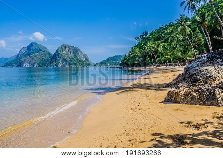 Sandy Beach with Palm Shadows, Huge Rocks in Background, El Nido, Palawan, Philippines.