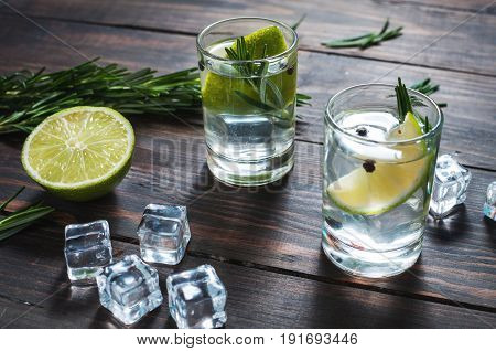 Alcoholic drink - gin tonic cocktail - with lime, rosemary and ice on rustic wooden table.