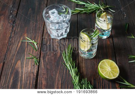 Alcoholic drink - gin tonic cocktail - with lime, rosemary and ice on rustic wooden table