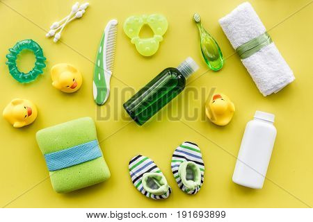 Baby care with bath cosmetic set, ducklings and towel on yellow background top view pattern
