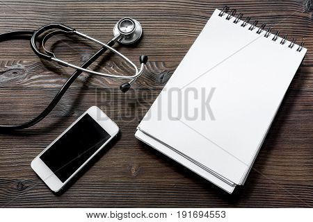 Make an appointment with doctor by cell phone dark wooden desk top view notebook.