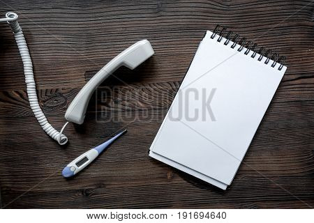 phone handset, thermometer and notebook on dark wooden desk top view call doctor.