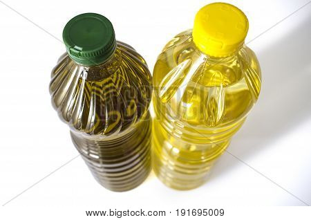 Olive versus sunflower oil bottled in PET. Upper area. Isolated over white