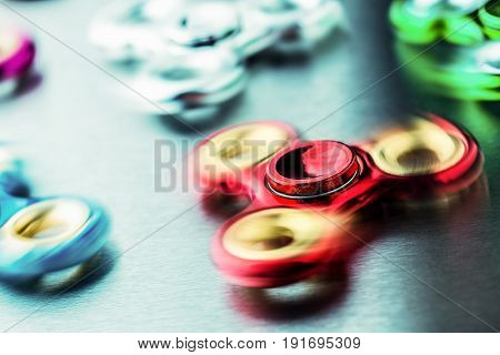 Fidget Spinner. Several colorful fidget spinners on a stainless steel plate.