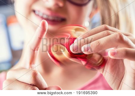 Fidget Spinner. Cute young girl playing with fidget spinner.