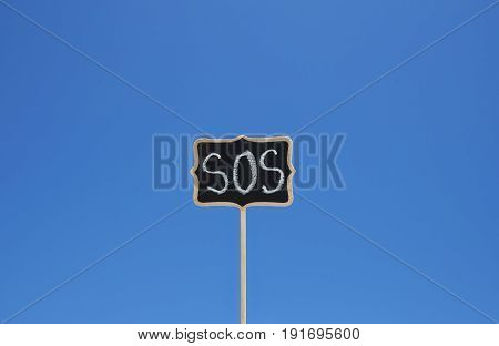Wooden plaque with the word sos against the blue sky