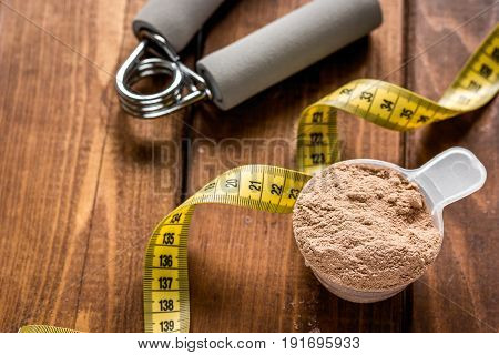 Whey protein powder for fitness nutrition to start training and measure tape on wooden background