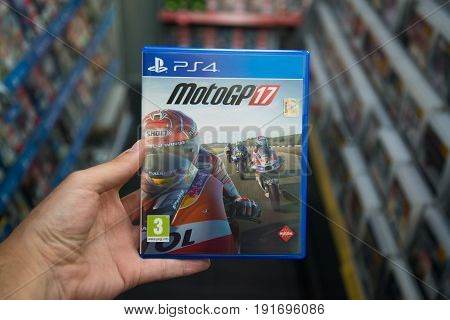 Bratislava, Slovakia, june 15, 2017: Man holding Motogp 17 videogame on Sony playstation 4 console in store