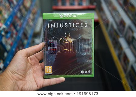 Bratislava, Slovakia, june 15, 2017: Man holding Injustice 2 videogame on Microsoft XBOX One console in store