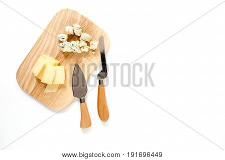 Aperitive parmesan cheese and cheese with blue mould on a cutting board on white background space for text.