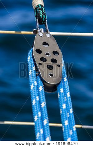 close-up of yacht pulley with blue rope