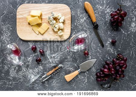 Appetizer parmesan cheese, cheese with blue mould and red grape on grey stone table background top view.