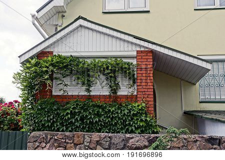 Veranda of a private house overgrown with green vegetation