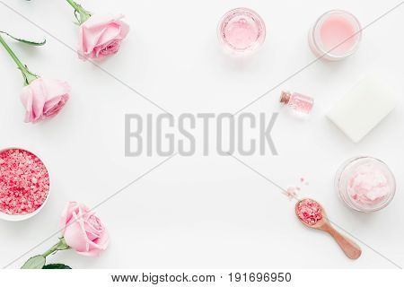 rose organic cosmetics with sea salt, cream and oil on white table background top view