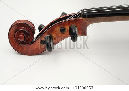 CLose up view of a violin with white plain background.