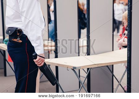 Security checks the metal detector against the background of scanning frames. Concept terrorism, terrorist attacks and explosions.