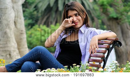 Tearful Youthful Female  Sitting in a Public Park