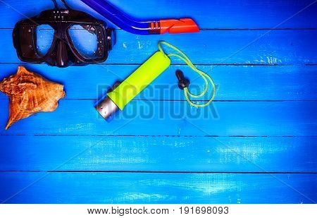 Mask with a tube for underwater diving on a blue wooden background empty space