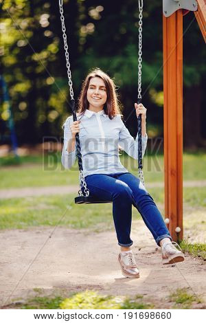 Girl student, teenager is smiling and swinging on a chain swing in the park. Concept is a playground for rest and a happy vacation in a new place.