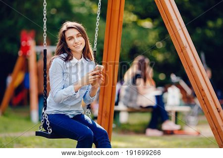 Girl student teenager swinging on a swing and using phone for communication looks in frame. Concept social networks and social activity by means of communication.