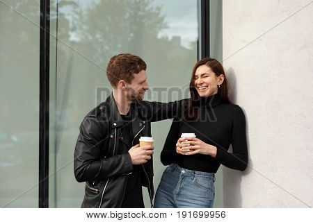 Happy young couple in love flirting on a first date on the street holding coffee cup in hands. Hipster girl laughs at a joke man while break at work in business centre. Love relashionship concept.