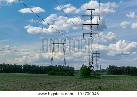 In the field there are towers for power transmission lines. Behind a blue sky with Cumulus clouds. You can see a lot of wires and several poles. In the background is the nuclear power plant.
