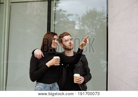 Handsome girl showing to her boyfriend interesting detail on the facade of the building walking in the new district of the city. Attractive tourists couple drinking coffee to go resting on the street