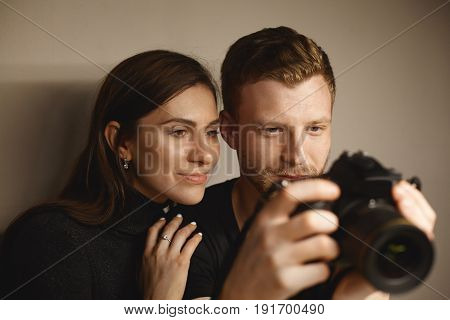 Indoor shot of young couple European appearance looking at camera's monitor cheking their photo session. Pretty brunette female and her blonde boyfriend looking pictures on professional photo camera