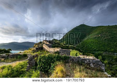 A traveler silhouette on the ruins of medieval fortress Mogren at the shore of Adriatic sea in Budva in Montenegro