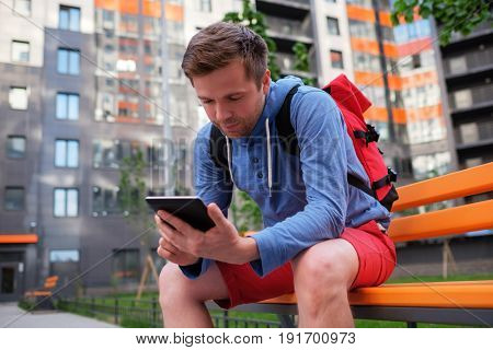 Portrait of mature man in casual clothing using digital tablet outdoors. Youngman sitting in city yard looking at his digital tab for directions and location.
