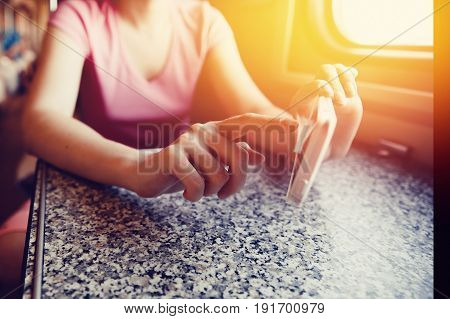 Girl is typing text on the phone - a computer smartphone in the train, subway, train. Concept of social mobility, the Internet, work as a freelancer.