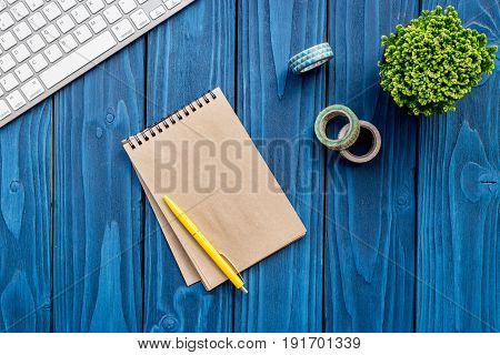 summer office desk at home with flowers, notebook and keyboard on blue wooden background top view space for text