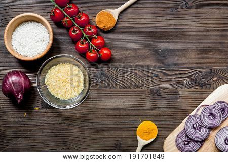 paella home cooking with rice, tomato, onion and spices for ingredients on wooden kitchen table background top view space for text