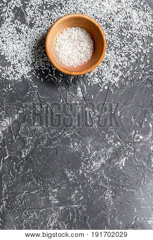 paella ingredients with rise in bowl on dark kitchen table background top view mock up