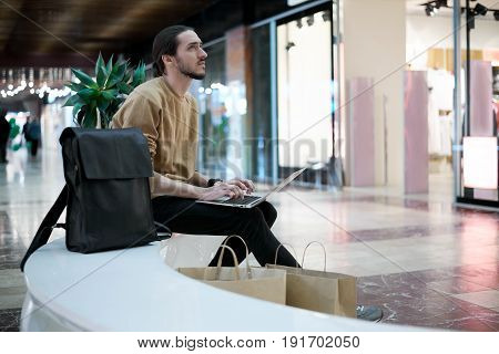Thoughtful beard freelancer designer have immediate work in shopping center. Man in swish and dark jeans sitting in front of shop with computer and use high technology to search information.