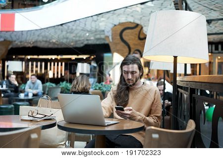 Serious hipster dialing numbers on mobile call to business partner and meet for a coffee break. Student use restaurant wifi connection to check email or surfing social networks and chat friends.