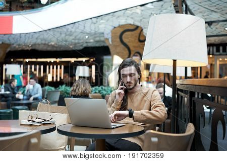 Young business man waiting for a meeting in cafe in shopping center Long hair guy talk bu phone and watch time. Student making freelance job out of home with laptop and wifi connection.