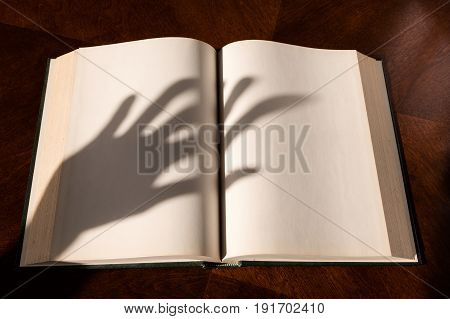 Blank white pages in an open hardcover book and hand shadow
