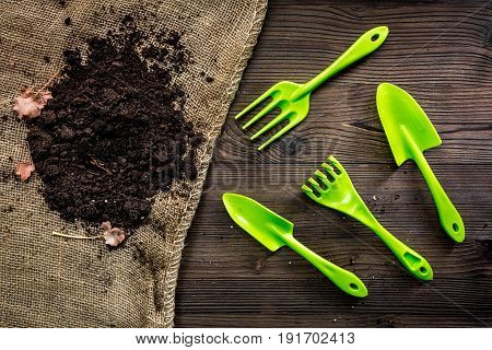green garden tools and ground for planting flowers at home on wooden table background top view