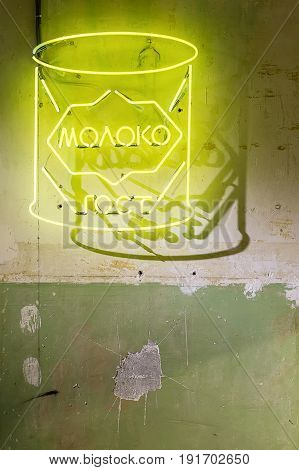 Luminous yellow signboard is hanging on the shabby wall. It drops shadow on the wall. Closeup. Vertical.
