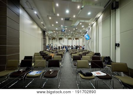 MOSCOW, RUSSIA - APR 25, 2017: Participants have snack at back of auditorium in Novotel Moscow City Hotel during AI Conference devoted to introduction of artificial intelligence into business.