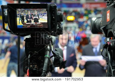 MOSCOW - APR 7, 2017: Commentators at camera display at basketball game Euroleague CSKA Moscow (Russia) - Olympiakos (Greece) in Megasport stadium