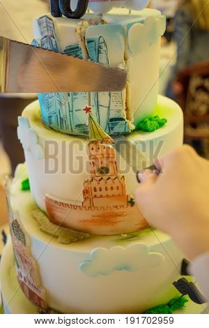 MOSCOW - APR 20, 2017: Big cake and hands with knifes at business conference Second breath of real estate market in Moscow business club in Congress-park Volynskoe